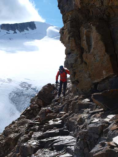 Mike traversing beneath a vertical cliff band. Mt. McArthur behind.