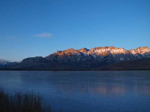 Miette Range rises behind the frozen Talbot Lake.