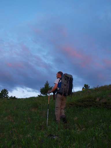 Ben hiking up the grassy slope