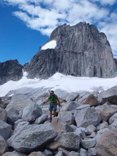 Eric hiking through a boulder field, with Snowpatch Spire behind
