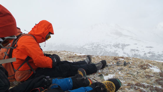 Sitting on the summit in order not to be blown off.