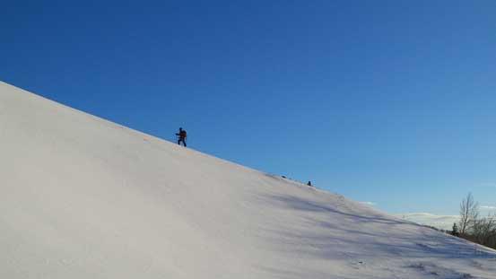 Grant snowshoeing up a snow ridge