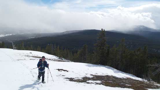 Grant snowshoeing up the summit ridge