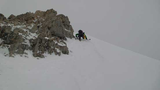 Down climbing steep snow to bypass the rock step on the lower ridge