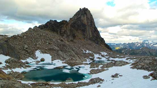 Eastpost Spire rises behind some tarns
