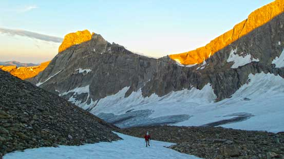 Ben hiking up a small snow patch, with more morning colours behind