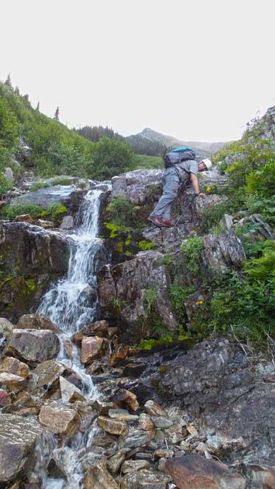 Eric down-climbing slippery terrain beside a mini waterfall