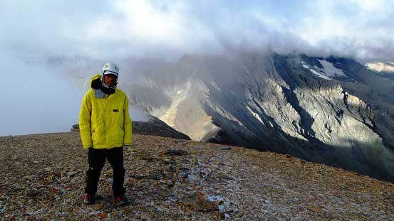 Me on the summit with Mt. Harrison in the background hidden in clouds