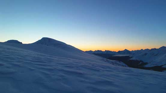 "Morning colours on the horizon. Ahead is the summit of the ""south pass peak""."