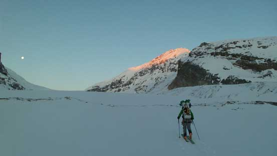Vern approaching the toe of Athabasca Glacier, with alpenglow on Snow Dome behind