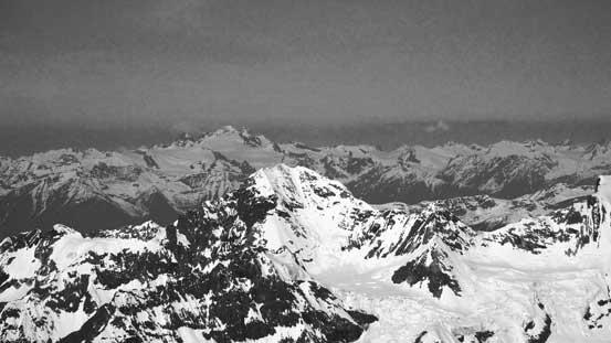 The Adament Group rises behind the summit of Rostrum Peak