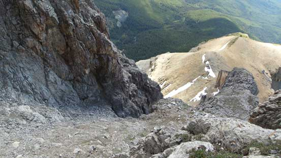 Looking down the scree bowl. It also shows the key (exposed) ledge traverse linking the bowl and the lower face