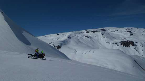 One of the many snowmobiles with the dome shaped Powder Mountain behind