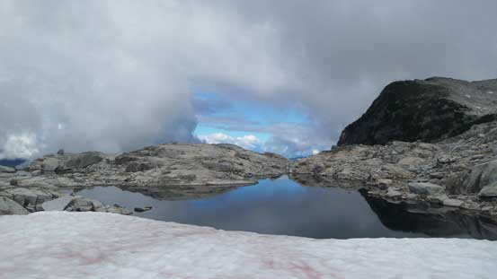 A neat tarn fed by a snowfield